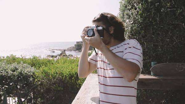 Young adult male takes pictures on a vintage 35mm film camera Royalty-free stock video