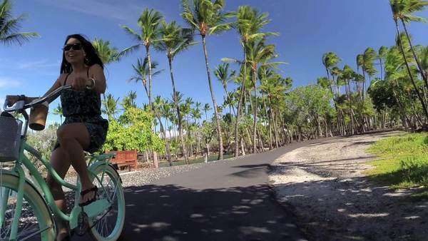 Woman riding a beach-cruiser bicycle on a sunny day in Hawaii. Royalty-free stock video