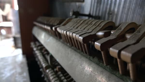 CLOSE UP, DOF: Old crumbling dusty piano from the inside  Hammers striking  strings tuned to produce the note when a piano key is pressed  Hammer falls
