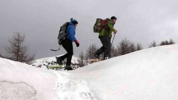 Wide shot of people walking in snowshoes Rights-managed stock video