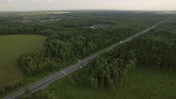 Aerial shot of transport traffic on the road in the countryside. Highway in the woods near the villages, Russia Royalty-free stock video