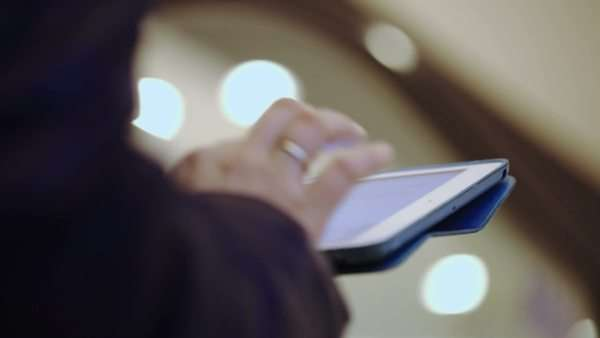 Close-up shot of woman typing on her tablet while riding on escalator. Defocused lights in background Royalty-free stock video