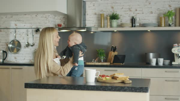 Young mother nursing her laughing child while standing in the kitchen Royalty-free stock video