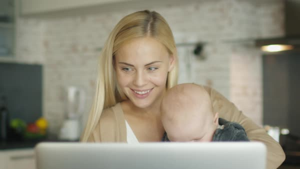 While sitting in the kitchen before laptop smiling mother holds baby in her arm and drinks from a cup Royalty-free stock video
