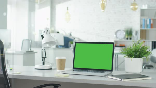 Creative office shot of green screened laptop standing on the table with nobody working on it. In the background man comes in and sits at his workplace starts working. Royalty-free stock video