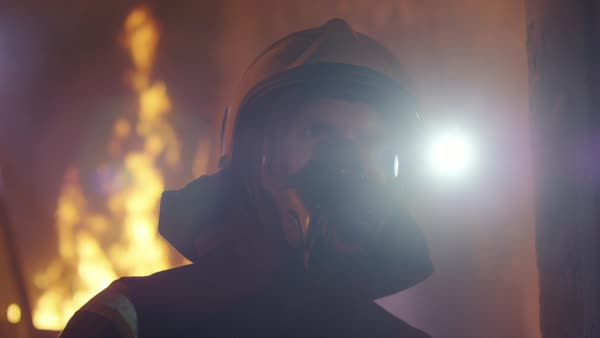 Portrait shot of a fireman standing in a burning building with fire raging behind him Royalty-free stock video