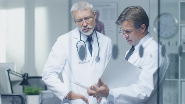 Two specialist doctors discussing patient's log. Both are senior and experienced. Their office looks modern and respectable. Royalty-free stock video