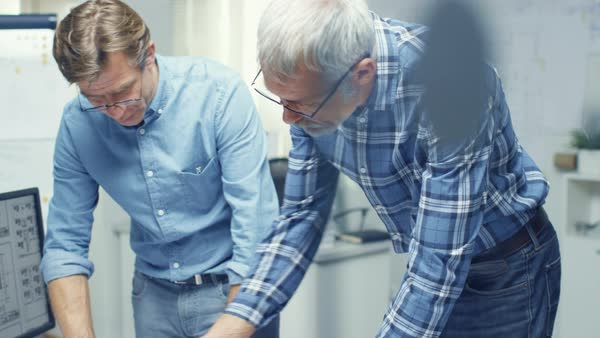 Two senior architectural engineers examine blueprints while standing over working table. They have discussion on the subject of various technical matters concerning pending project. Royalty-free stock video