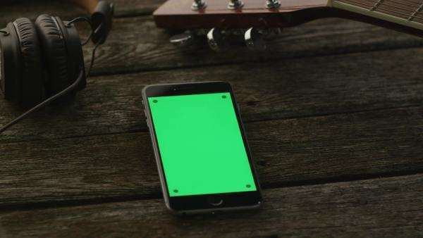Phone with green screen in portrait mode laying on wooden table next to guitar and headphones. Royalty-free stock video