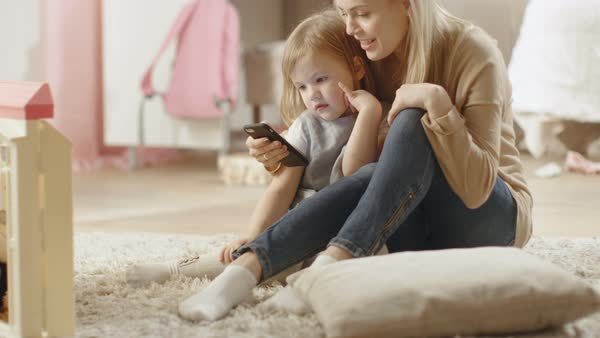 Beautiful young mother sits with her little daugher and shows her something interesting on a smartphone. Children's room is pink and full of toys. Royalty-free stock video
