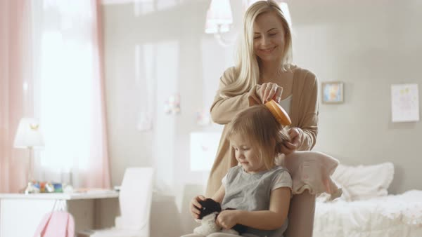Sweet young mother brushes hair of her cute little blonde daughter. Slow motion. Royalty-free stock video