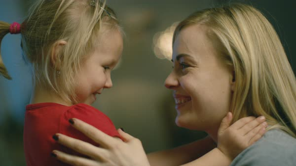 Close-up shot of a beautiful mother holding her cute blonde daughter and smiling. Royalty-free stock video