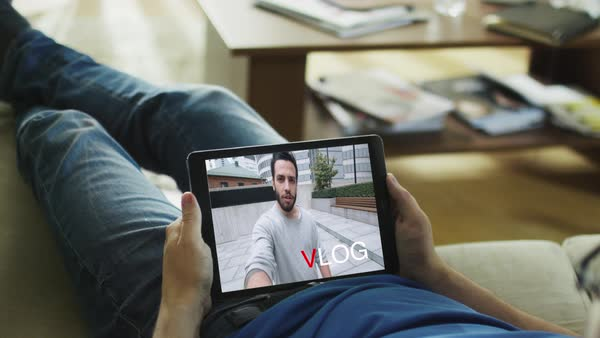 "Casual man lying on his couch watching fashionable video blogg on his tablet computer. Inscription ""vlog"" appears on the screen. Royalty-free stock video"