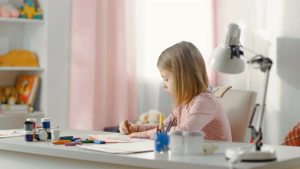 Sweet little girl draws with crayons in her light room. Royalty-free stock video