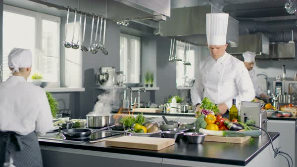 Chef Works in a Big Restaurant Kitchen with His Apprentices. Kitchen is Full of Food, Vegetables and Pans on Fire. Royalty-free stock video