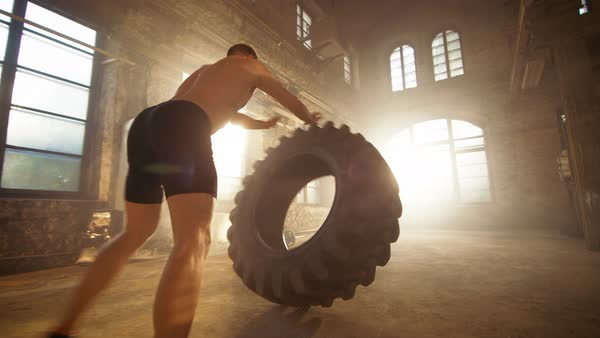 Strong muscular man lifts tire as part of his fitness program Royalty-free stock video
