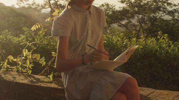Girl is drawing in a notebook at sunset time Royalty-free stock video