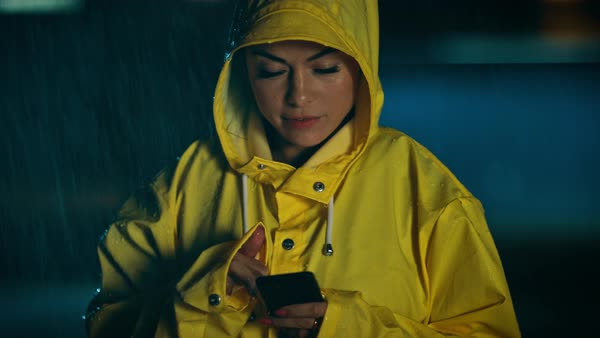 03758c7dc Beautiful concentrated young girl in a yellow raincoat is using a  smartphone in the rain. weather is rainy and it's night time.