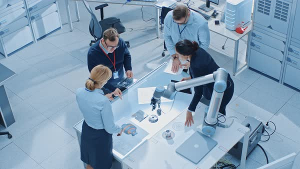 Team of industrial robotics engineers gathered around table with robot arm,  they use tablet computer to manipulate and program it to pick up and move
