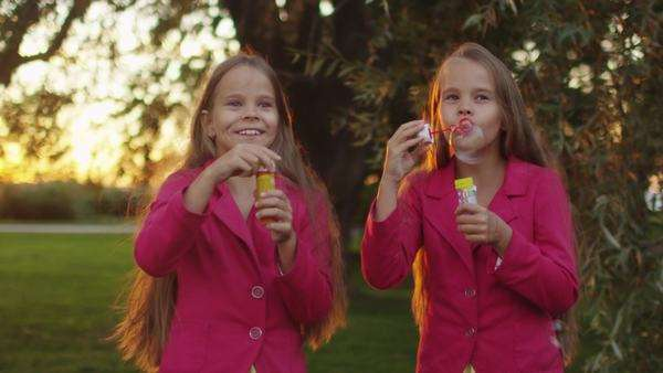 Two twin girls are playing with soap bubbles at park Royalty-free stock video