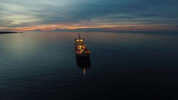 Aerial orbit shot of tanker ship moving in sea at night Royalty-free stock video