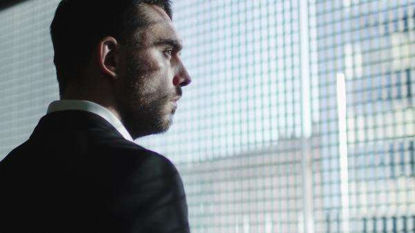 Businessman in a suit looks out of a big window in a city on a sunny day. Royalty-free stock video