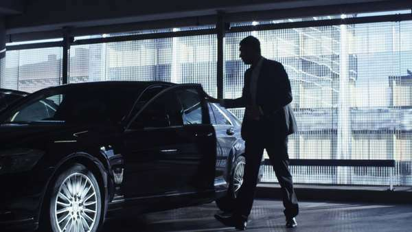 Businessman in a suit gets out of a black executive car in a garage parking lot. Royalty-free stock video