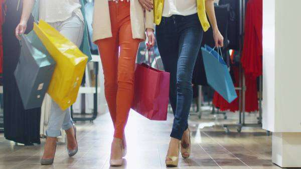 Low shot of female legs walking through a department store in colorful garments. Royalty-free stock video