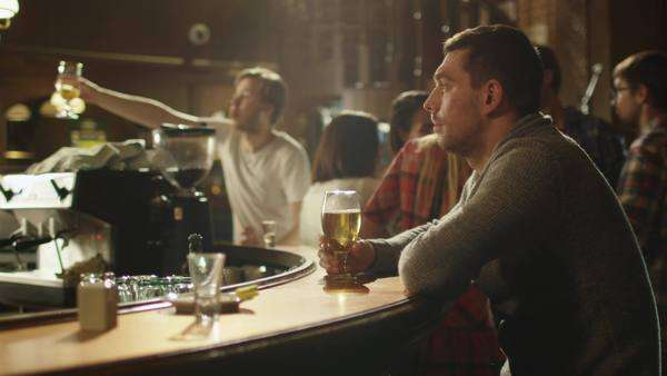 Man sitting alone with beer in a bar while people are having good time. Royalty-free stock video