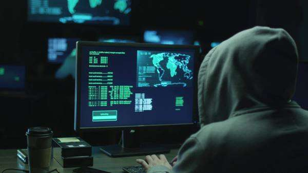 Male hacker in a hood works on a computer with maps and data on display screens in a dark office room. Royalty-free stock video