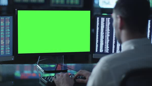 Man is working on a computer with mock-up green screen in a dark office filled with displays. Royalty-free stock video