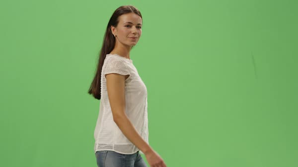 Casual young brunette girl is walking on a mock-up green screen in the background. Royalty-free stock video