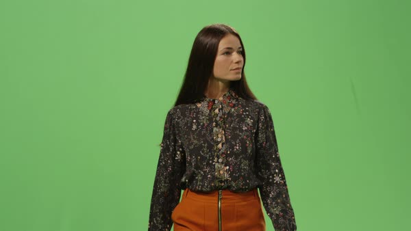 Casual brunette woman is walking on a mock-up green screen in the background. Royalty-free stock video
