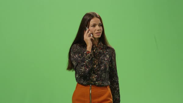 Casual brunette woman is walking and talking on the phone on a mock-up green screen in the background. Royalty-free stock video