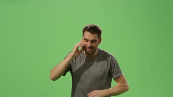 Man in a t-shirt is jogging while speaking on the mobile phone on a mock-up green screen in the background. Royalty-free stock video