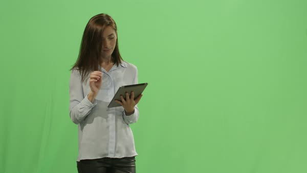Woman is using a tablet computer on a mock-up green screen in the background. Royalty-free stock video