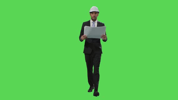 Businessman in a hard hat and a suit is walking with papers on a mock-up green screen in the background. Royalty-free stock video