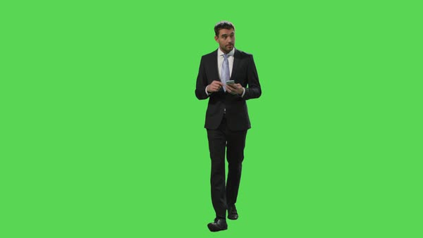 Businessman in a suit is using a smartphone while walking on a mock-up green screen in the background. Royalty-free stock video