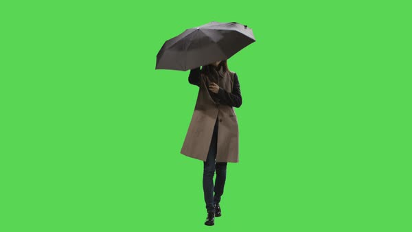 Casual brunette woman is noticing the rain while walking and opens an umbrella on a mock-up green screen in the background. Royalty-free stock video