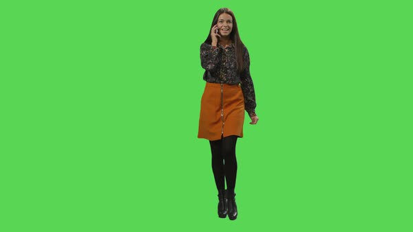 Casual brunette girl is walking and talking on the phone on a mock-up green screen in the background. Royalty-free stock video