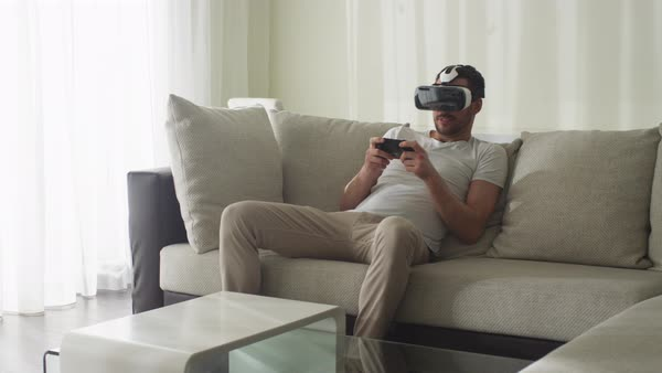 Man wearing vr headset and playing games with controller at living room. Royalty-free stock video