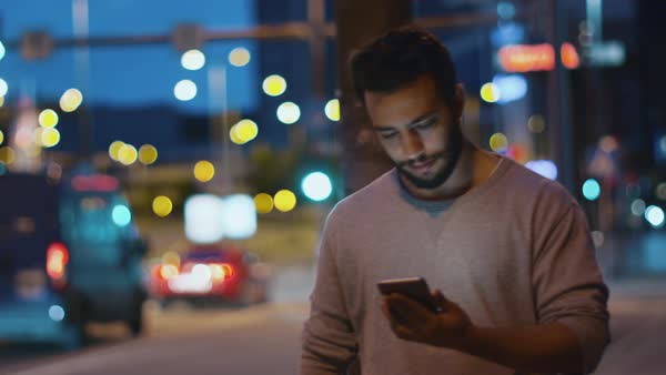 Attractive man using mobile phone walking along urban street during evening. Royalty-free stock video