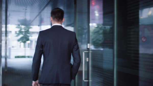 Follow shot of businessman walking on streets of business district. Royalty-free stock video