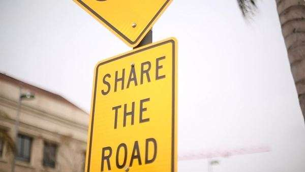 Close up shot of a road sign asking drivers to share the road with cyclists Royalty-free stock video
