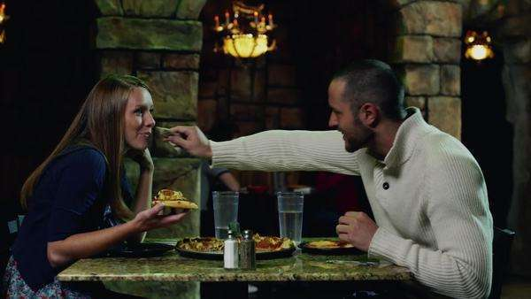 Medium shot of couple eating pizza in restaurant Royalty-free stock video