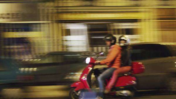 Wide shot pan of Night street scene with couple on moped, Paris, France Royalty-free stock video