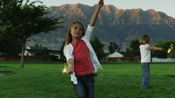 Wide shot of two girls playing with sparklers in park at dusk, Utah Royalty-free stock video