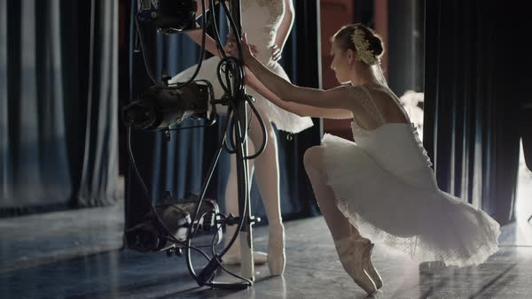 Medium panning shot of ballerina stretching en pointe backstage Rights-managed stock video