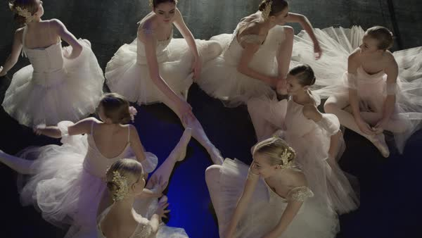 Medium high angle shot of ballerinas sitting on floor warming up Rights-managed stock video