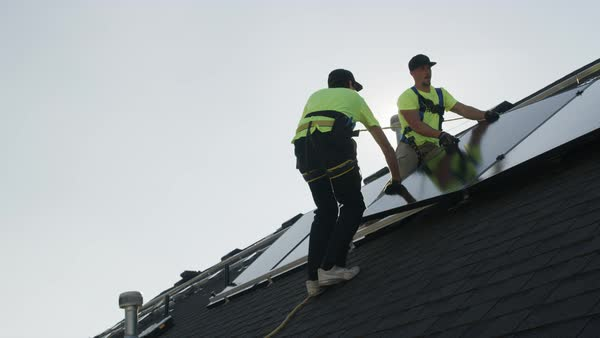 Medium panning low angle shot of workers installing solar panel on roof Royalty-free stock video